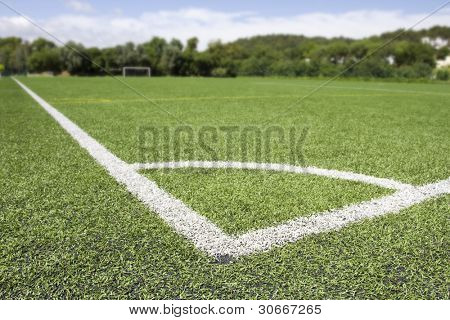 Green grass and corner lines of an outdoor football field (artificial covering) - blured at background