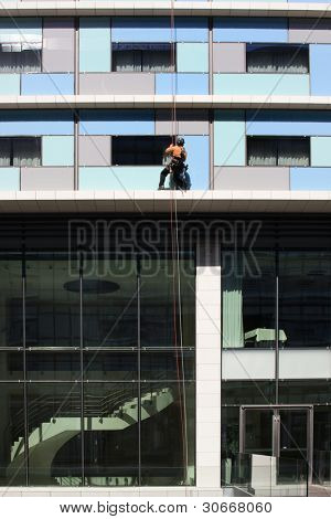 Worker washing the windows facade of a modern office building (cleaning glass service)