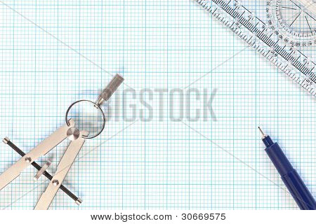 Still life photo of engineering graph paper with a fine 0.1mm pen, compass and protractor ruler, blank to add your own design, image or text.