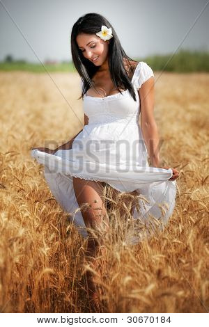 Happy beautiful woman in grain rural field