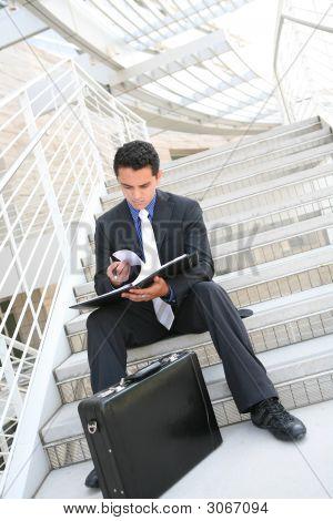 Hombre de negocios en escaleras revisar notas