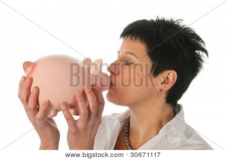 Young woman holding and kissing a piggy bank as studio portrait
