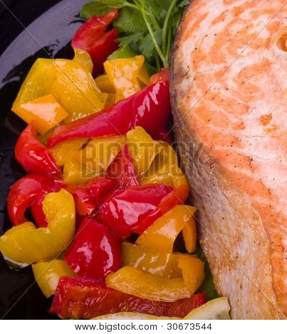 Fried salmon with grilled vegetable on a black plate