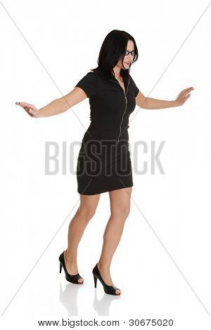 Young businesswoman balancing, like she was walking on rope, isolated on white background