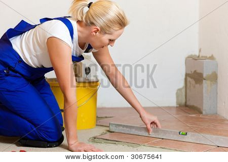 Female construction worker is tiling at home; she is presumably a do-it-yourself