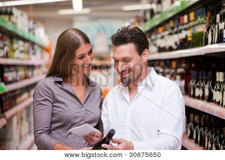 Feliz pareja joven sonriendo mientras que las compras de vino junto al supermercado