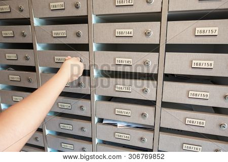 poster of Close-Up of Woman Hand Insert a Key to Unlock Mailbox Locker in Apartment, Interior Mail Letterbox Cabinet in Condominium. Row of Post Locker in Residential Building.
