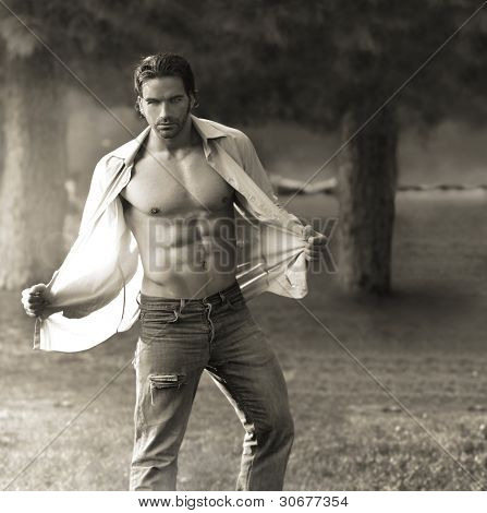 Classic portrait of muscular man outdoors opening his shirt