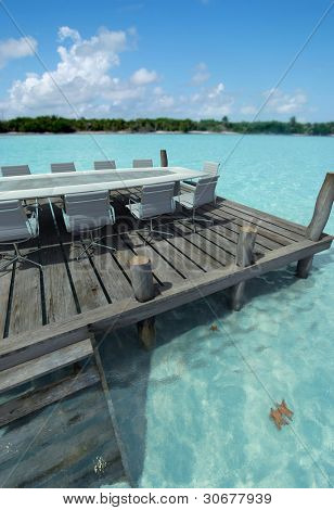 Business meeting table on a peer by an idyllic beach