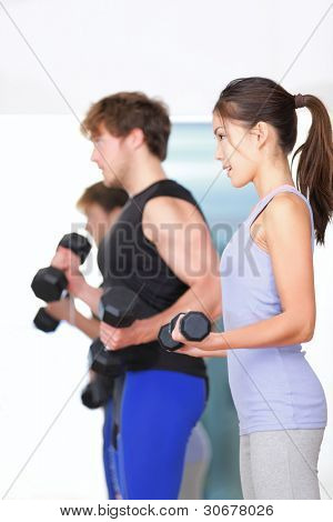 Fitness people in gym. Couple strength training lifting weights during indoor fitness workout. Woman lifting dumbbells training biceps in focus.