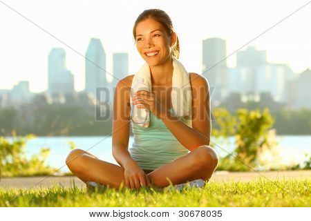 Outdoor workout woman. Fitness woman runner relaxing drinking water after training outside in city park with skyline. Beautiful young multiracial sport model in Montreal, Quebec, Canada at sunset.
