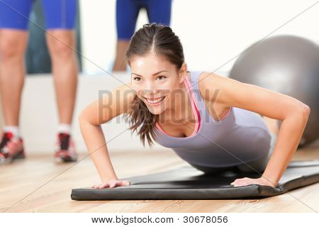 Gym woman working out doing push-ups strength training smiling happy during workout. Young mixed race fitness model training in fitness center.