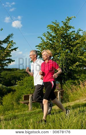 Mature or senior couple doing sport outdoors, jogging down a path in summer