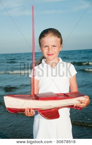Lovely girl with yacht model on the beach