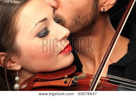 Beautiful lady with handsome man with violin over black background