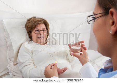 Doctor Giving Medication To Senior Patient