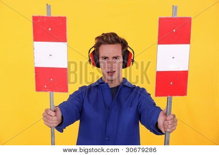 craftsman holding two road signs