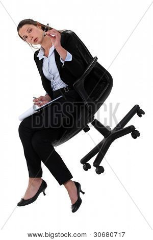 Businesswoman sat in chair taking notes
