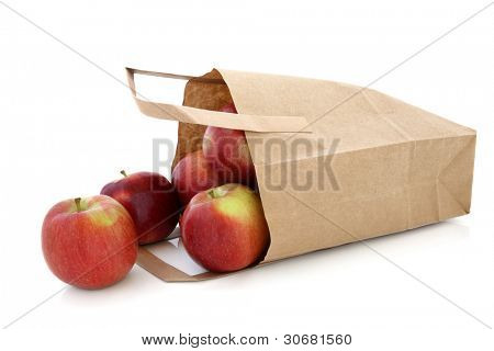 Apple fruit in a brown paper recycled carrier bag isolated over white background. Red Dessert variety.