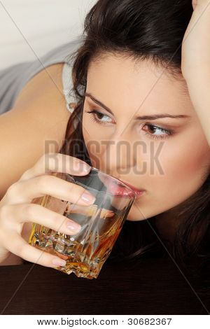 Young beautiful woman in depression, drinking alcohol