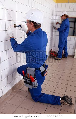 Male and female electricians at work