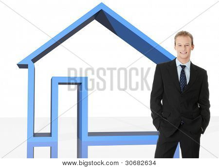 Young businessman standing in front of big blue 3d home. Real estate or insurance concept