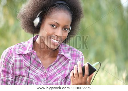 beautiful black woman listening music in the park