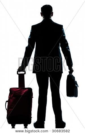 rear view one caucasian business traveler man walking with suitcase standing  full length silhouette in studio isolated white backgroun
