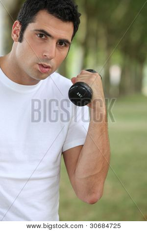 Man lifting dumbbell outdoors