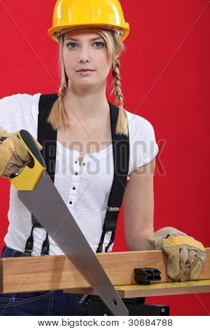 Female carpenter sawing.