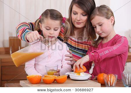 Familie quetschen frischen gepresster Orangensaft