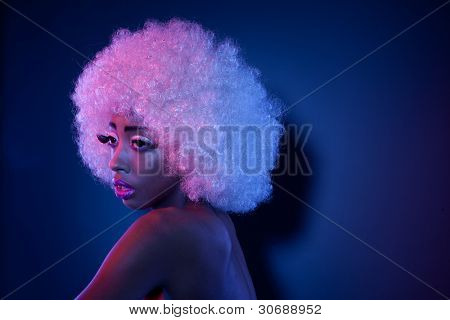 Attractive African model in creative makeup and a large curly white Afro style wig looking out of frame with copyspace behind.
