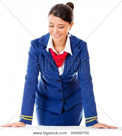 Air hostess leaning on a table - isolated over a white background