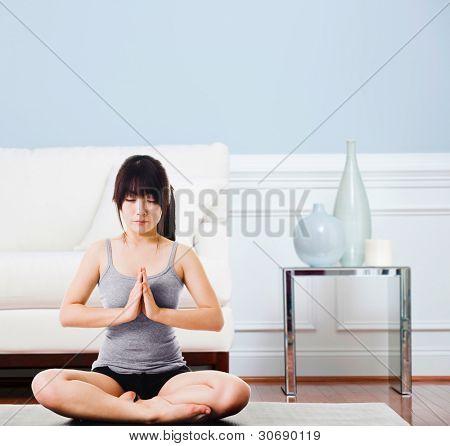 Asiatische Frau sitzt auf einer Yogamatte tun das Anrede-Siegel darstellen. Meditation.