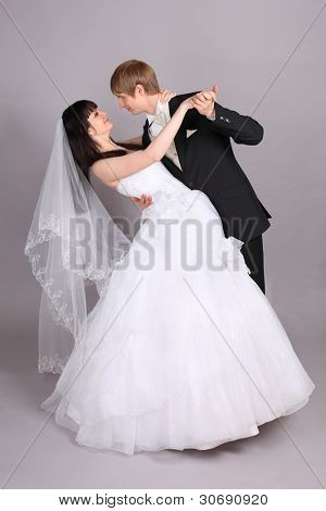 Groom and beautiful bride dance in studio on gray background