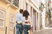 Multiethnic Couple Of Tourists Walking Through Old City And Doing Sightseeing. Backs Of Afro America poster
