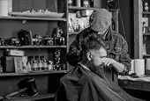 Hipster Client Getting Haircut. Barber With Hair Clipper Works On Haircut Of Bearded Guy Barbershop  poster