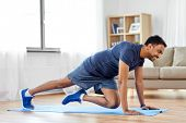 sport, fitness and healthy lifestyle concept - man doing running plank exercise at home poster