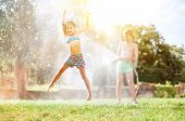 Happy Little Girl Jumps Under Water, When Brother Pours Her From Garden Hose. Hot Summer Days Activi poster