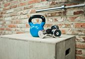 Functional Training Concept. Kettlebell, Dumbbell Stand On Wooden Box Against The Brick Wall Backgro poster
