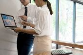 Business Businessman And Woman Stand In Meeting Analyses, On The Table Have Chart Graphy Marketing P poster