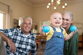 Happy baby playing with balls on floor with grandparents in background. Cute boy standing and holdin poster