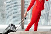Close-up The Hand Holding The Handle Suitcase. Businesswoman Arrives In A Hotel Room With Black Suit poster