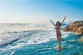 A Girl In A Swimsuit, Splashing From The Waves, Brunette Girl Rejoices Splashing From The Waves. You poster