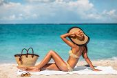 Sexy bikini woman tanning relaxing on beach. Suntan concept. Unrecognizable female adult from the ba poster
