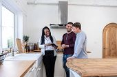 African American Female Real Estate Agent In Kitchen Showing Gay Couple Around New House poster