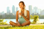 Outdoor workout woman. Fitness woman runner relaxing drinking water after training outside in city p