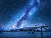 Bridge And Starry Sky With Milky Way Over Snow Covered Mountains Reflected In Water. Night Landscape poster