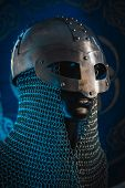 Triskel, Vikings, viking helmet with chain mail on a red shield with golden shapes of sun, weapons f poster