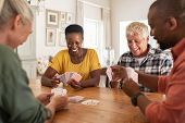 Retired multiethnic people playing cards together at home. Happy senior friends with african couple  poster